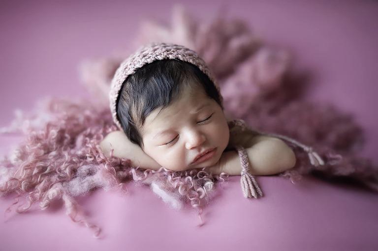 Pink blanket surrounding newborn sleeping on blanket