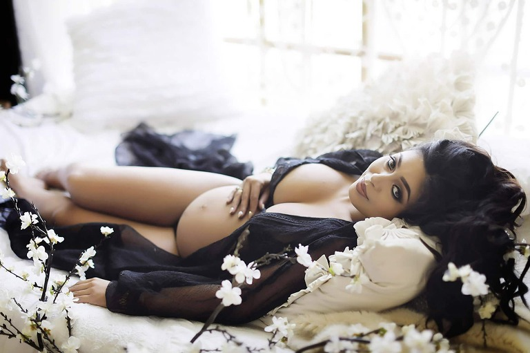 Boudoir photograph of woman posing in bed with flowers and sexy outfit